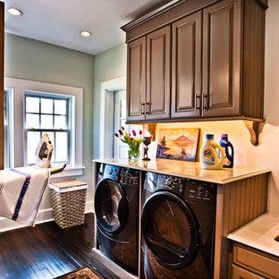 Immagine di una lavanderia chic con ante in legno bruno, lavatrice e asciugatrice affiancate, pavimento marrone e top beige