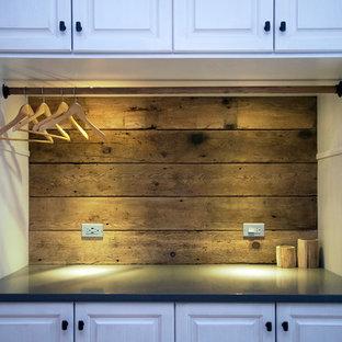 Immagine di una lavanderia rustica con ante in stile shaker, ante bianche, top in quarzite, pareti grigie e lavatrice e asciugatrice nascoste
