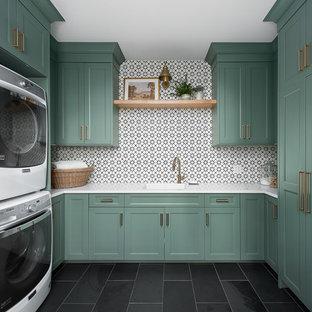 シカゴの中サイズのトランジショナルスタイルのおしゃれな家事室 (アンダーカウンターシンク、緑のキャビネット、クオーツストーンカウンター、磁器タイルの床、上下配置の洗濯機・乾燥機、黒い床、白いキッチンカウンター、落し込みパネル扉のキャビネット) の写真