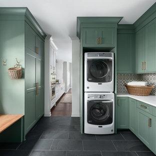 Immagine di una lavanderia multiuso classica di medie dimensioni con lavello sottopiano, ante in stile shaker, ante verdi, top in quarzo composito, pareti bianche, pavimento in gres porcellanato, lavatrice e asciugatrice a colonna, pavimento nero e top bianco