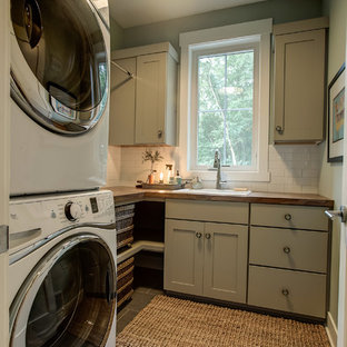 Small 1950s l-shaped beige floor dedicated laundry room photo in Grand Rapids with a drop-in sink, shaker cabinets, beige cabinets, wood countertops, gray walls and a stacked washer/dryer