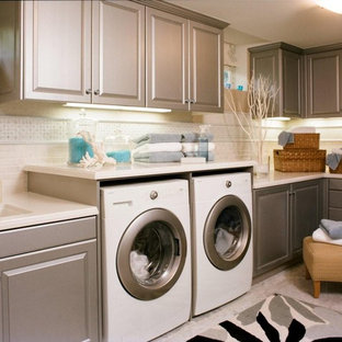 Laundry room - traditional gray floor laundry room idea in Los Angeles with an undermount sink, raised-panel cabinets, gray cabinets and a side-by-side washer/dryer