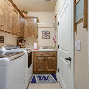 Cette photo montre une petit buanderie craftsman dédiée avec un évier 2 bacs, des portes de placard en bois brun, un mur beige et des machines côte à côte.