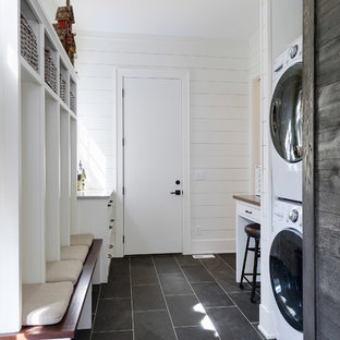 Photo of a large nautical galley utility room in Minneapolis with white cabinets, wood worktops, white walls, slate flooring, a stacked washer and dryer and grey floors.