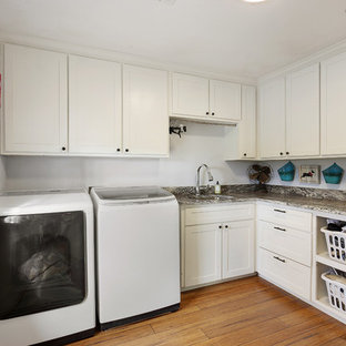 This is an example of a large classic l-shaped separated utility room in New Orleans with a submerged sink, shaker cabinets, white cabinets, granite worktops, white walls, a side by side washer and dryer, medium hardwood flooring and brown floors.