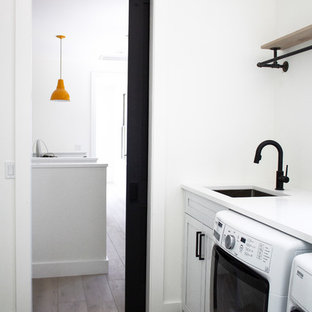 Mid-sized danish galley vinyl floor dedicated laundry room photo in New York with an undermount sink, shaker cabinets, white cabinets, quartz countertops, white walls, a side-by-side washer/dryer and white countertops