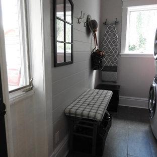 Inredning av ett klassiskt litet svart linjärt svart grovkök, med en undermonterad diskho, skåp i shakerstil, röda skåp, bänkskiva i kvarts, vitt stänkskydd, stänkskydd i stenkakel, vita väggar, klinkergolv i keramik, en tvättpelare och grått golv