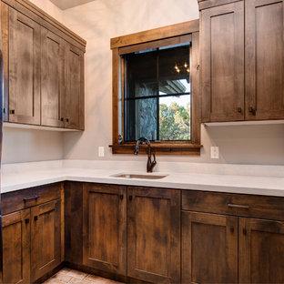 Idee per una lavanderia multiuso chic con lavello da incasso, ante con riquadro incassato, ante in legno bruno, pareti bianche, lavatrice e asciugatrice a colonna, pavimento arancione, top bianco e pavimento in mattoni