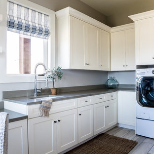Example of a large cottage l-shaped porcelain floor dedicated laundry room design in Salt Lake City with an undermount sink, recessed-panel cabinets, beige cabinets, gray walls, a side-by-side washer/dryer, quartz countertops and gray countertops