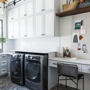 Inredning av en lantlig mellanstor vita u-formad vitt tvättstuga enbart för tvätt, med vita väggar, en tvättmaskin och torktumlare bredvid varandra, skåp i shakerstil, grå skåp och grått golv