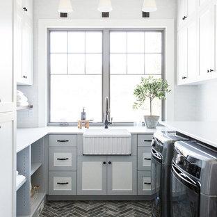 Bild på en mellanstor lantlig vita u-formad vitt tvättstuga enbart för tvätt, med vita väggar och en tvättmaskin och torktumlare bredvid varandra