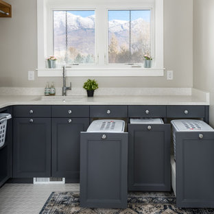 Transitional l-shaped white floor dedicated laundry room photo in Salt Lake City with an undermount sink, recessed-panel cabinets, gray cabinets, gray walls and beige countertops