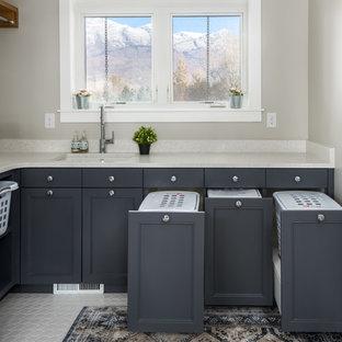 Idéer för att renovera en vintage beige l-formad beige tvättstuga enbart för tvätt, med en undermonterad diskho, luckor med infälld panel, grå skåp, grå väggar och vitt golv