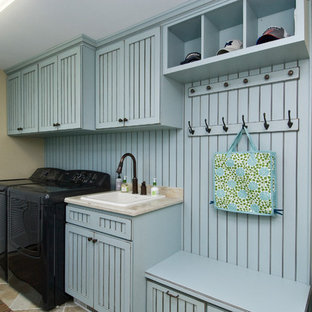 Example of a mid-sized classic single-wall porcelain tile and beige floor utility room design in Other with a drop-in sink, blue cabinets, granite countertops, beige walls, a side-by-side washer/dryer, beige countertops and recessed-panel cabinets