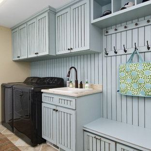 Mid-sized elegant single-wall porcelain floor and beige floor utility room photo in Other with blue cabinets, a drop-in sink, granite countertops, beige walls, a side-by-side washer/dryer, beige countertops and recessed-panel cabinets