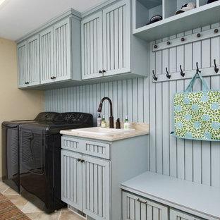 Foto di una lavanderia multiuso classica di medie dimensioni con ante blu, lavello da incasso, top in granito, pareti beige, pavimento in gres porcellanato, lavatrice e asciugatrice affiancate, pavimento beige, top beige e ante con riquadro incassato