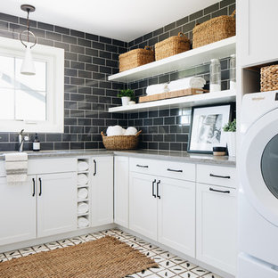Example of a cottage l-shaped white floor utility room design in Chicago with an undermount sink, shaker cabinets, white cabinets, black walls, a side-by-side washer/dryer and gray countertops