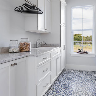 Inspiration for a large beach style single-wall dedicated laundry room in Tampa with a drop-in sink, shaker cabinets, white cabinets, marble benchtops, white splashback, porcelain floors, a concealed washer and dryer, multi-coloured floor, grey benchtop and vaulted.