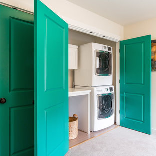 This is an example of a mid-sized transitional laundry cupboard in Seattle with beige walls, carpet and a stacked washer and dryer.