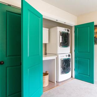 Foto di un ripostiglio-lavanderia classico di medie dimensioni con pareti beige, moquette e lavatrice e asciugatrice a colonna