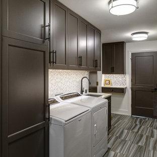 Inspiration för mellanstora klassiska linjära flerfärgat tvättstugor enbart för tvätt, med en undermonterad diskho, skåp i shakerstil, bruna skåp, bänkskiva i kvarts, flerfärgad stänkskydd, flerfärgade väggar, en tvättmaskin och torktumlare bredvid varandra och flerfärgat golv