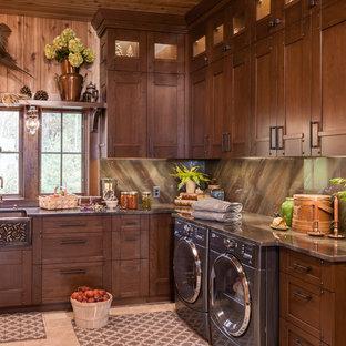 他の地域の大きいトラディショナルスタイルのおしゃれな洗濯室 (エプロンフロントシンク、ベージュの床、落し込みパネル扉のキャビネット、オニキスカウンター、ベージュの壁、磁器タイルの床、左右配置の洗濯機・乾燥機、茶色いキッチンカウンター、濃色木目調キャビネット) の写真