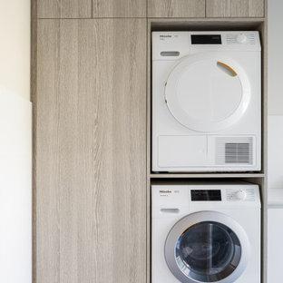 Ispirazione per una lavanderia multiuso design di medie dimensioni con lavello sottopiano, ante lisce, top in quarzo composito, paraspruzzi bianco, paraspruzzi in gres porcellanato, pavimento in gres porcellanato, lavatrice e asciugatrice a colonna, pavimento grigio e top bianco
