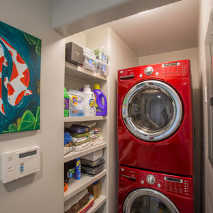 Immagine di una piccola sala lavanderia tropicale con pareti bianche e lavatrice e asciugatrice a colonna