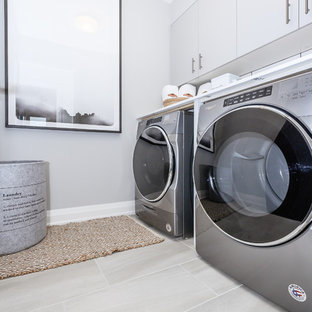 Design ideas for a large contemporary utility room in Toronto with flat-panel cabinets, grey walls, porcelain flooring and grey floors.