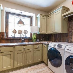 Immagine di una lavanderia multiuso rustica di medie dimensioni con lavello da incasso, ante lisce, top piastrellato, pareti marroni, pavimento con piastrelle in ceramica, lavatrice e asciugatrice affiancate e ante beige