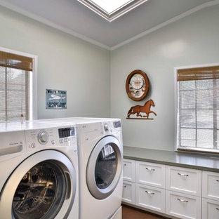 Modelo de cuarto de lavado ecléctico, de tamaño medio, con suelo de cemento, lavadora y secadora juntas, suelo marrón, encimeras grises, armarios estilo shaker y puertas de armario blancas