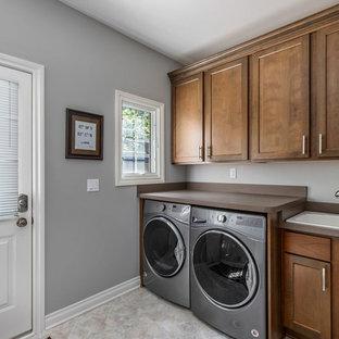 Foto de lavadero ecléctico con fregadero encastrado, armarios estilo shaker, puertas de armario de madera oscura, encimera de laminado, paredes grises, suelo vinílico, lavadora y secadora juntas, suelo multicolor y encimeras marrones