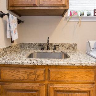 Exempel på en klassisk beige beige tvättstuga, med en enkel diskho, granitbänkskiva och beige stänkskydd