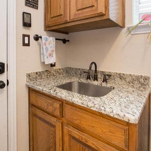 Foto på en vintage beige tvättstuga, med en enkel diskho, granitbänkskiva och beige stänkskydd