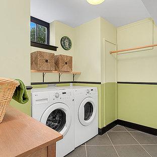 Immagine di una sala lavanderia etnica con pareti verdi, lavatrice e asciugatrice affiancate e pavimento grigio