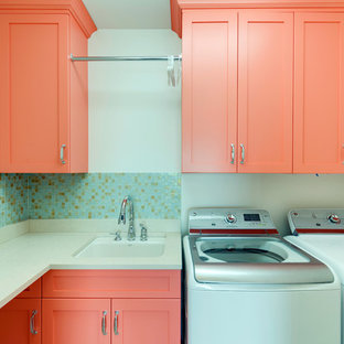 Mid-sized contemporary l-shaped dedicated laundry room in Charlotte with recessed-panel cabinets, orange cabinets, limestone benchtops, white walls, a side-by-side washer and dryer and an undermount sink.