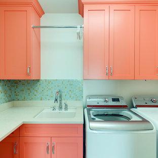 Ispirazione per una sala lavanderia design di medie dimensioni con ante con riquadro incassato, ante arancioni, top in pietra calcarea, pareti bianche, lavatrice e asciugatrice affiancate e lavello sottopiano