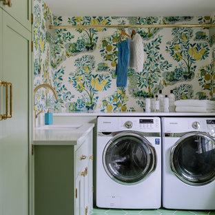 Klassisk inredning av en vita l-formad vitt tvättstuga enbart för tvätt, med skåp i shakerstil, gröna skåp, flerfärgade väggar, en tvättmaskin och torktumlare bredvid varandra och grönt golv