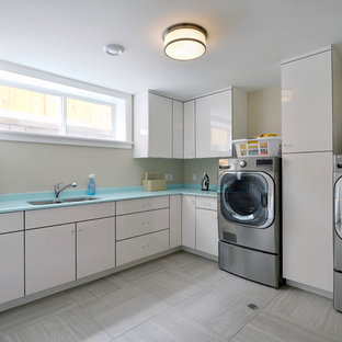 Inspiration for a contemporary l-shaped gray floor dedicated laundry room remodel in Other with an undermount sink, flat-panel cabinets, white cabinets, beige walls, a side-by-side washer/dryer and blue countertops