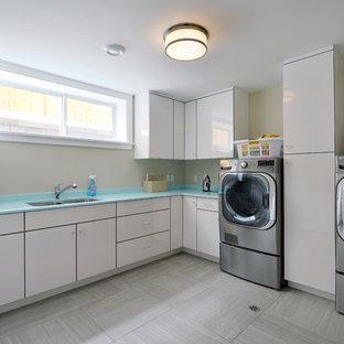 Inredning av en modern blå l-formad blått tvättstuga enbart för tvätt, med en undermonterad diskho, släta luckor, vita skåp, beige väggar, en tvättmaskin och torktumlare bredvid varandra och grått golv