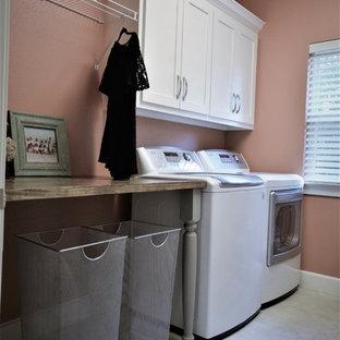 Ispirazione per una piccola lavanderia classica con ante in stile shaker, ante bianche, top in legno, pavimento in travertino, lavatrice e asciugatrice affiancate, pavimento bianco e pareti rosa