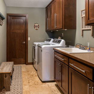 Photo of a mid-sized country galley utility room in Minneapolis with a drop-in sink, shaker cabinets, dark wood cabinets, quartz benchtops, brown splashback, green walls, travertine floors, a side-by-side washer and dryer, multi-coloured floor and beige benchtop.