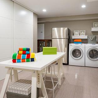 Inredning av ett modernt stort grovkök, med grå väggar, en tvättmaskin och torktumlare bredvid varandra, grått golv och laminatgolv