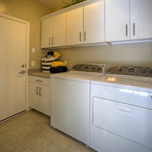 Foto på en liten funkis linjär tvättstuga enbart för tvätt, med släta luckor, vita skåp, laminatbänkskiva, beige väggar, klinkergolv i keramik och en tvättmaskin och torktumlare bredvid varandra