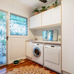 Exempel på en mellanstor retro flerfärgade linjär flerfärgat tvättstuga, med en nedsänkt diskho, vita skåp, bänkskiva i terrazo, vitt stänkskydd, stänkskydd i mosaik, vita väggar, mörkt trägolv, en tvättmaskin och torktumlare bredvid varandra och brunt golv