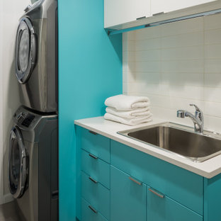 Photo of a mid-sized midcentury galley dedicated laundry room in Vancouver with a drop-in sink, flat-panel cabinets, turquoise cabinets, quartzite benchtops, white walls, porcelain floors, a stacked washer and dryer, grey floor and white benchtop.