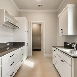 Idéer för en stor klassisk parallell tvättstuga enbart för tvätt, med en undermonterad diskho, släta luckor, vita skåp, bänkskiva i kvarts, grå väggar, klinkergolv i keramik och en tvättmaskin och torktumlare bredvid varandra