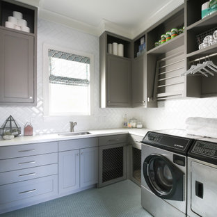 Inspiration for a large transitional l-shaped gray floor dedicated laundry room remodel in Houston with an undermount sink, shaker cabinets, gray cabinets, white backsplash, a side-by-side washer/dryer and white countertops