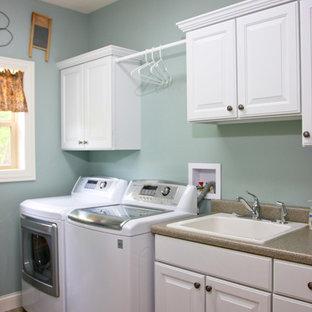Inspiration för en mellanstor vintage linjär tvättstuga enbart för tvätt, med luckor med upphöjd panel, vita skåp, laminatbänkskiva, linoleumgolv, en tvättmaskin och torktumlare bredvid varandra, en nedsänkt diskho och blå väggar