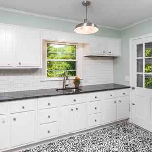 Esempio di un'ampia lavanderia multiuso classica con lavello sottopiano, ante lisce, ante bianche, top in granito, pareti verdi, pavimento con piastrelle in ceramica, lavatrice e asciugatrice affiancate, pavimento multicolore e top nero